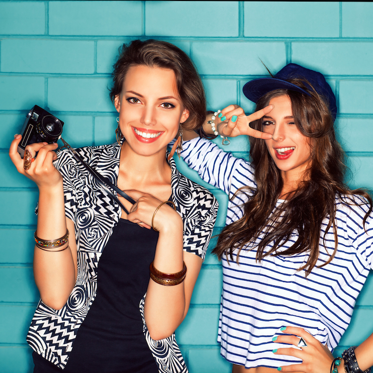 a girl with a camera and her friend smile for the camera in front of light blue brick wall